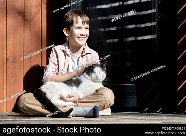Smiling boy looking away while stroking cat relaxing on him at porch during sunny day, Tarusa, Russia
