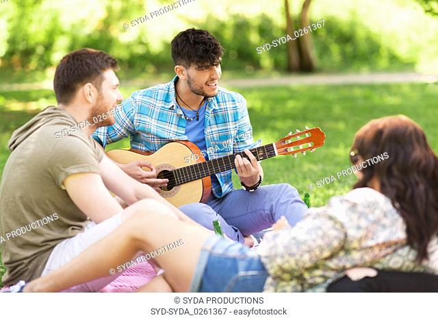 friends playing guitar at picnic in summer park