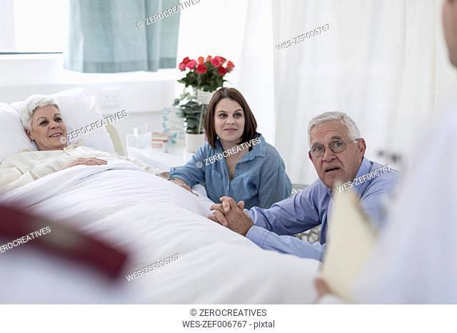 Family visiting senior patient and looking to doctor in hospital