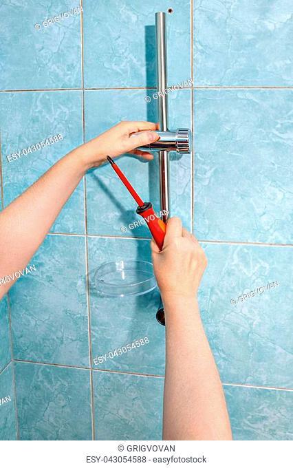 Residential plumbing repair, close-up install hand held shower head holder