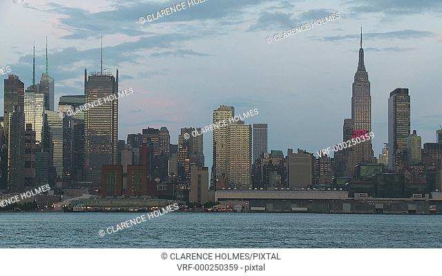 A view of the Empire State Building, Hudson River, and mid-town Manhattan skyline in New York City during late afternoon
