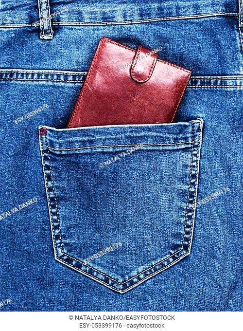 brown leather purse lies in the back pocket of blue jeans, full frame