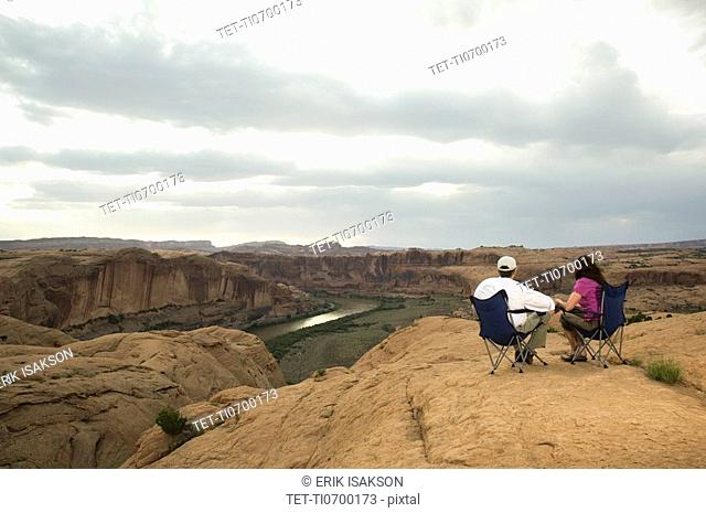 Couple in camping chairs over-looking canyon