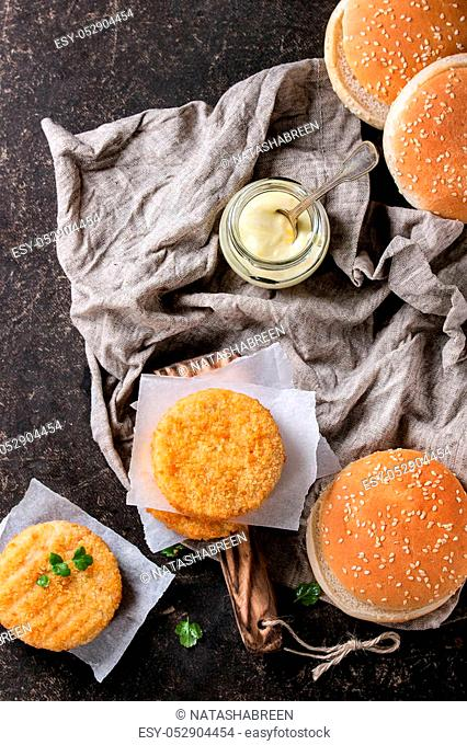 Ingredients for making vegan burger. Veggie cheese and onion cutlets, yogurt sauce, hamburger buns and herbs, served on wooden board with textile on dark...