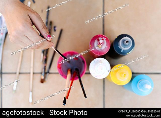 hand removing a brush in the water to clean the color painting with some paint bottles on the floor of a terrace. Overhead horizontal photo
