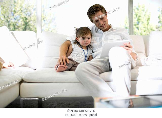 Father using digital tablet with baby girl on sofa