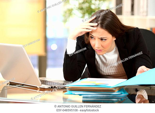 Worried businesswoman with a difficult job watching her laptop on line in a desk at office
