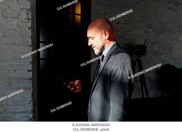 Portrait of businessman looking down at smartphone