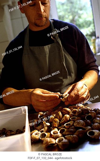 Close-up of a mid adult man cleaning seashells
