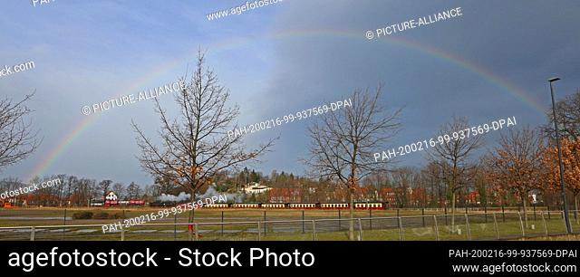 16 February 2020, Saxony-Anhalt, Wernigerode: A rainbow can be seen in spring-like weather over a train of the Harzer Schmalspurbahnen GmbH in Wernigerode