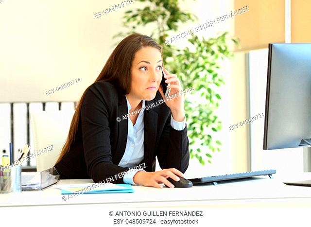 Confused office worker calling on phone checking computer content