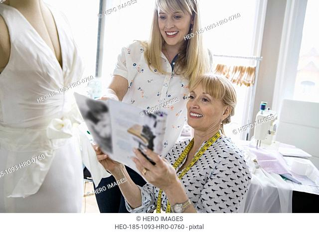 Seamstress and daughter looking at wedding magazine