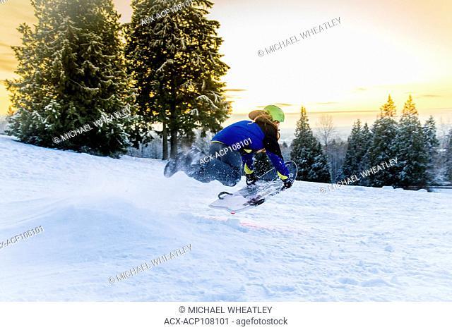 Boy sledding on Burnaby Mountain, Burnaby, British Columbia, Canada. (model released Cedar Bricker)