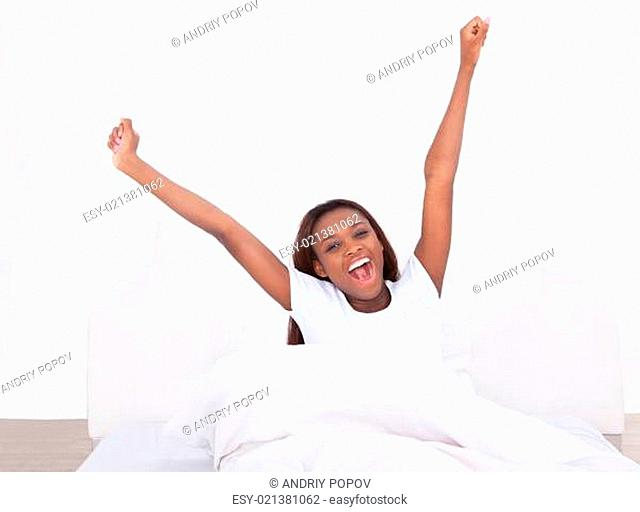 Young African American woman stretching in bed at home