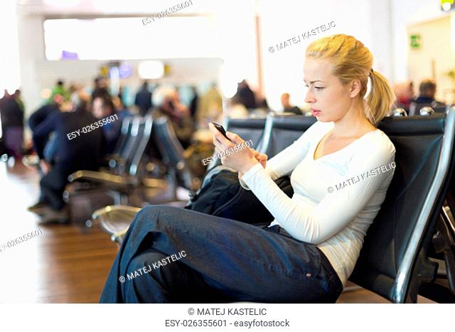 Casual blond young woman using her cell phone while waiting to board a plane at the departure gates. Wireless network hotspot enabling people to access internet...
