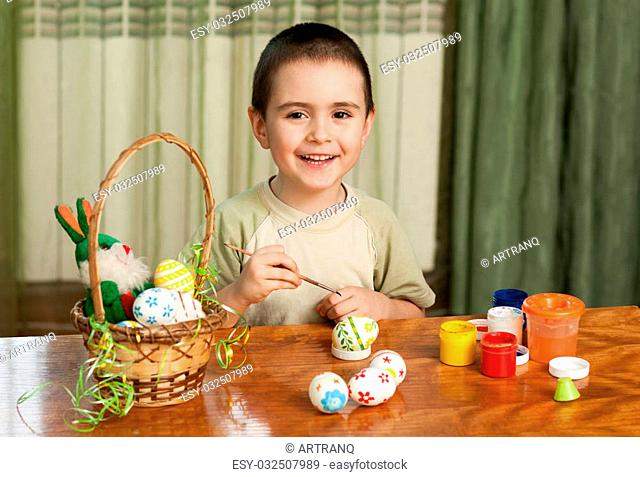 funny boy colored Easter eggs sitting at the table