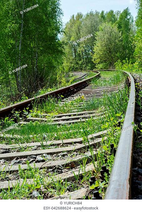 Abandoned railroad overgrown with grass and winding among trees. Abrupt turn of abandoned railroad