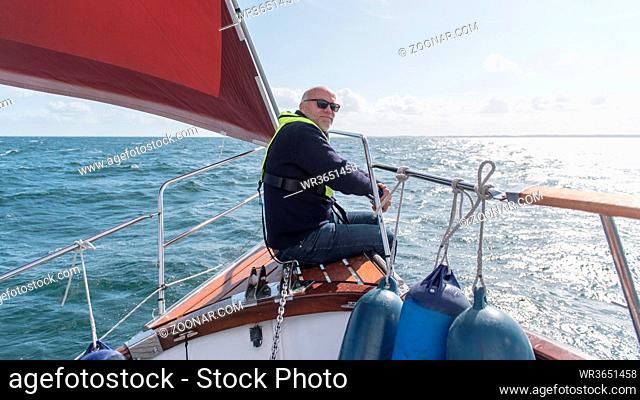 Skipper im Bugkorb seiner Segelyacht. Skipper in pulpit of his sailing boat