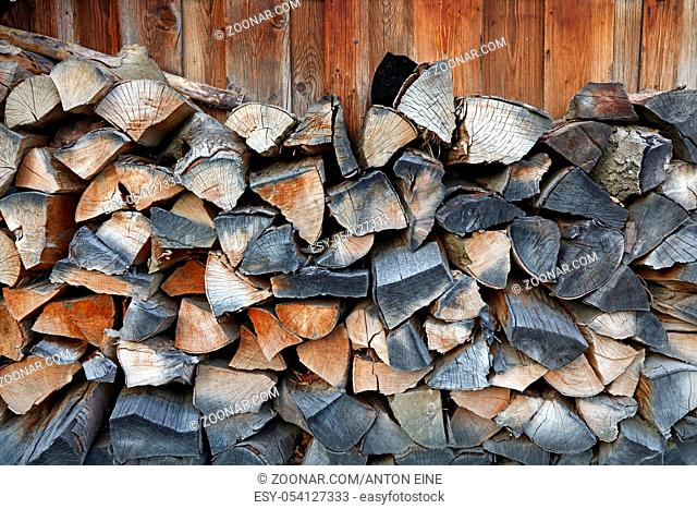 Firewood stock for traditional natural winter fireplace split chop wood fuel arranged in woodpile stack heap, close up