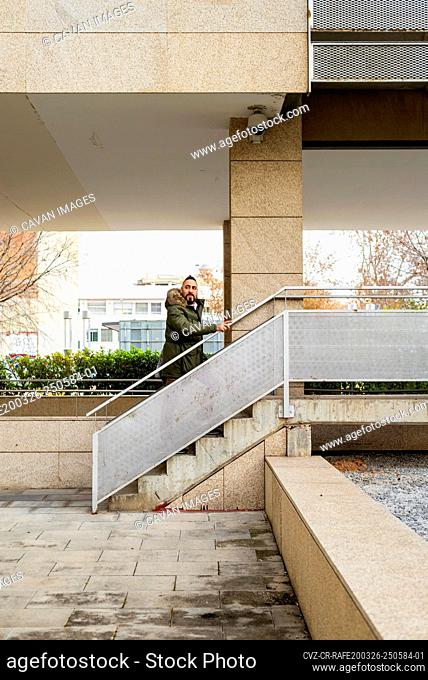 Bearded man with coat walking up stairs and looking away