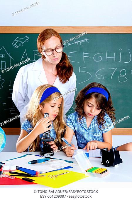 kids students with nerd teacher woman at science school classroom