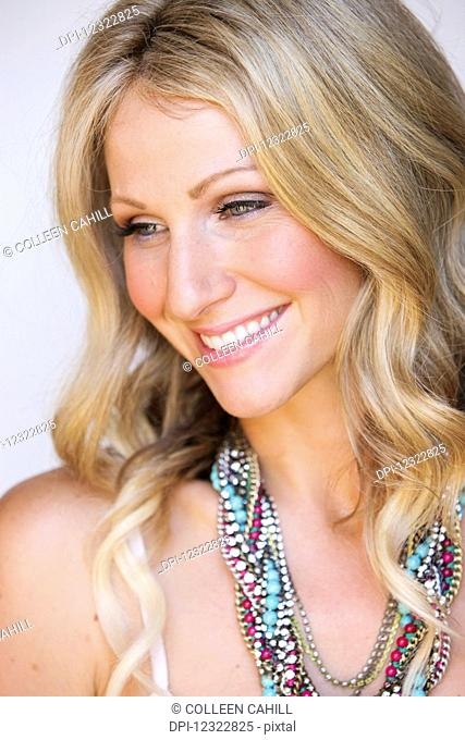 Portrait of a woman with long blond hair and a colourful beaded necklace against a white background; Oregon, United States of America