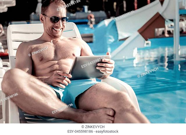 Joyful activity. Cheerful gentleman wearing sunglasses lying on a sunbed and smiling while focusing his attention on a screen of his tablet computer