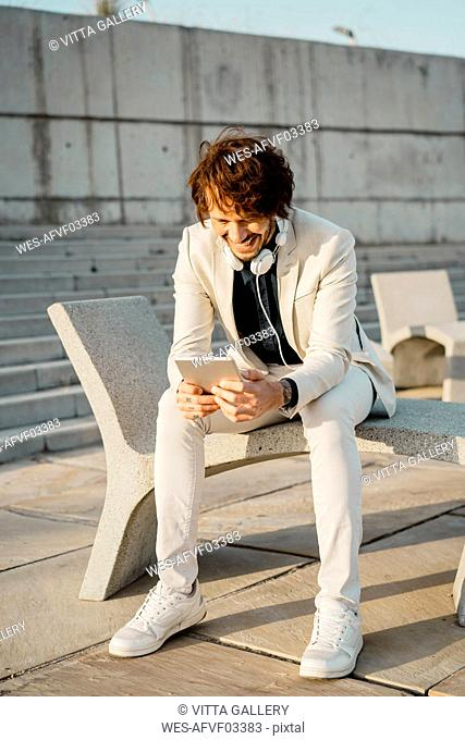 Laughing businessman using digital tablet outdoors