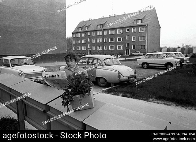 """05 May 1985, Saxony, Radefeld: A young woman reads in the newspaper """"""""Freiheit"""""""" (district newspaper of the SED Halle) She is standing at the mailbox in the..."""