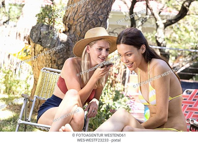 Two young women in garden sharing cell phone