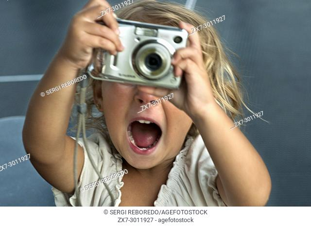 A two year old girl holding a digital snapshot camera and smiling