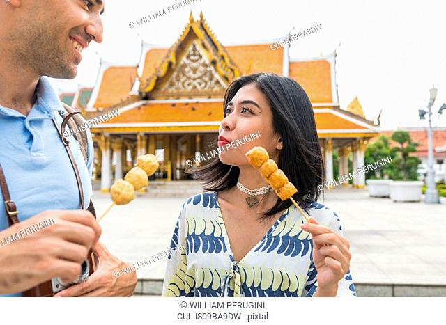 Young tourist couple eating skewered street food outside temple, Bangkok, Thailand