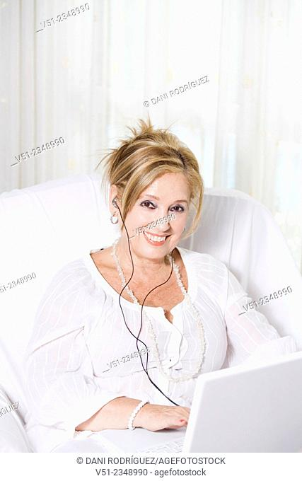 Senior woman on the couch with laptop, listening to music and smiling at camera