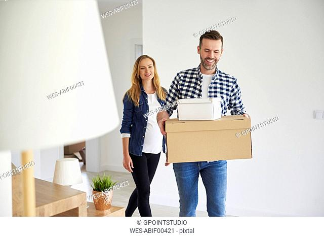 Happy couple moving into new flat carrying cardboard box