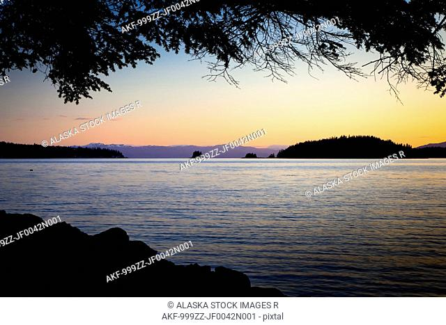 The silhouette of Betton Island at sunset across Clover Passage with tree branches in foreground, Ketchikan, Southeast Alaska, Spring