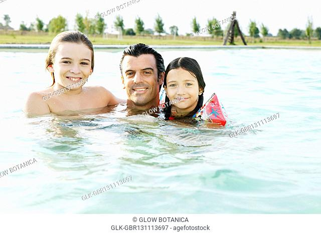 Man and his two children smiling in a swimming pool