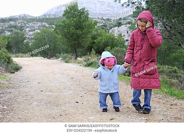 Girl (8) holding hand of a toddler (12 months) on a forest path, Provence, France