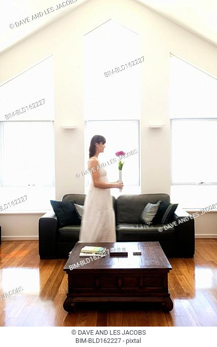 Caucasian woman carrying flowers in living room