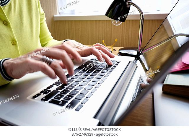 View of woman's hands with ring, with laptop computer and table lamp