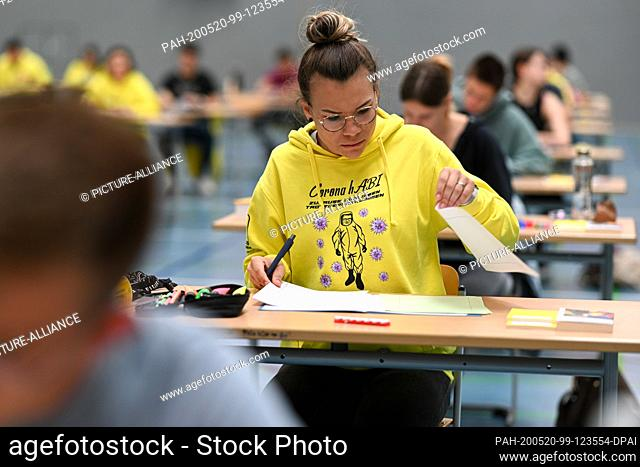 20 May 2020, Baden-Wuerttemberg, Ravensburg: A pupil is looking at the assignments during the German final examination in the sports hall of the...