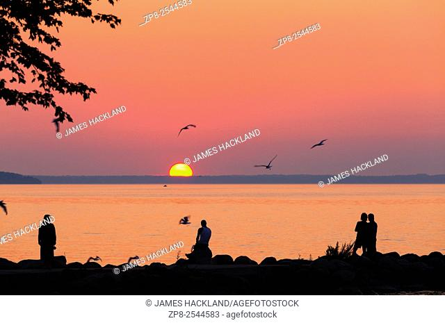 People silhouetted against a vibrant sky as the sun sets over Lake Simcoe. Willow Beach, Ontario, Canada