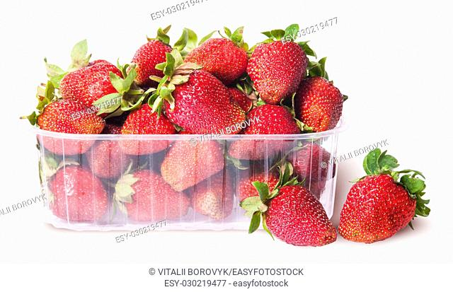 Freshly strawberries in a plastic tray and two near isolated on white background