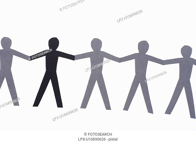 One black cutout paper person holding hands with group of white people