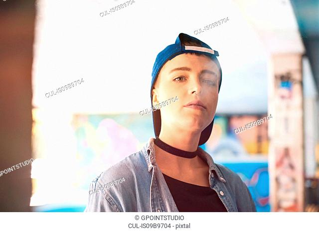 Portrait of young female skateboarder wearing baseball cap and smoking at skateboarding park