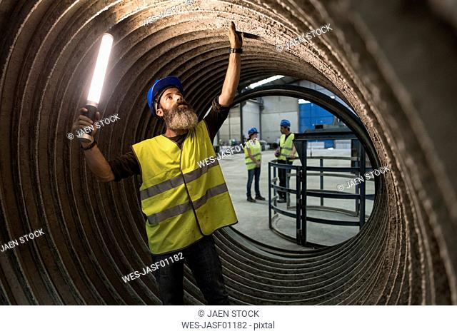 Worker examining giant construction tube