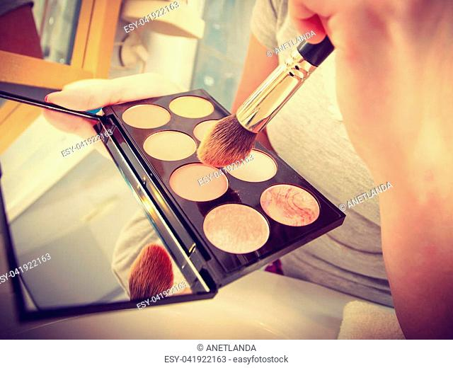 Contouring face kit, visage and make up concept. Woman in bathroom applying contour bronzer on brush
