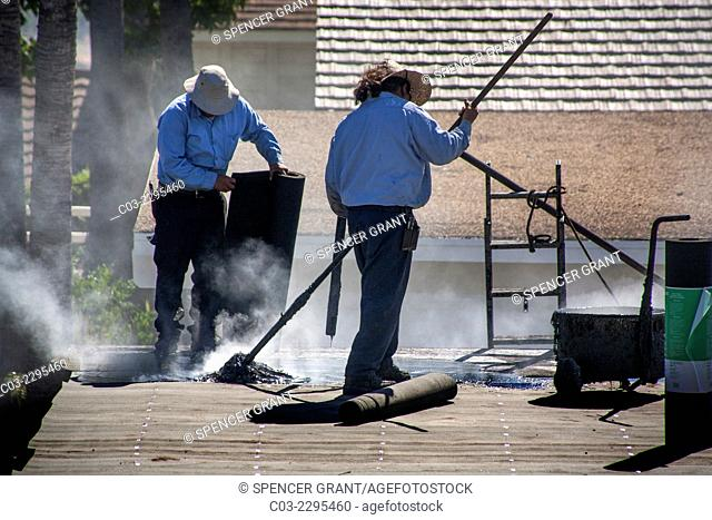 Steam rises from hot tar as Hispanic workmen replace a garage roof in Laguna Niguel, CA. Note rolls of tar paper