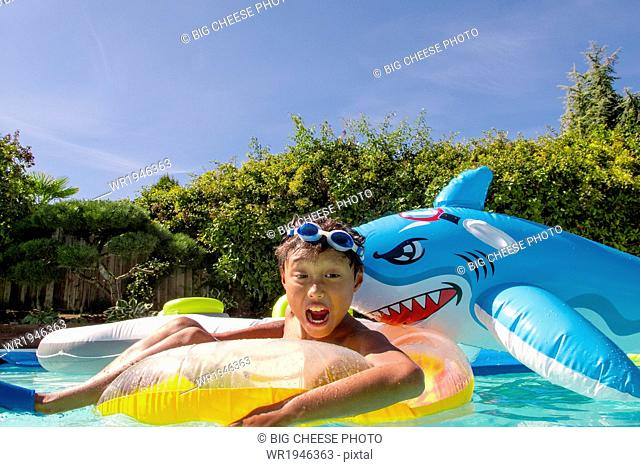 Boy pretends to be attacked by an inflatable shark in a pool