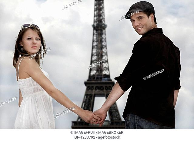 Young couple, hand in hand in front of the Eiffel Tower, Paris, France, Europe