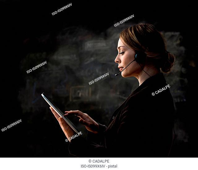 Businesswoman wearing telephone headset using digital tablet